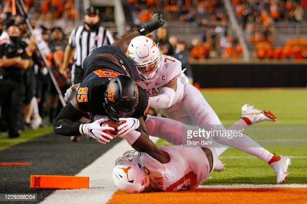 Tight end Jelani Woods of the Oklahoma State Cowboys dives into the end zone for a nullified overtime touchdown against defensive back Caden Sterns...