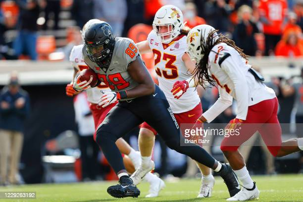 Tight end Jelani Woods of the Oklahoma State Cowboys runs his way to a 34-yard touchdown on a catch against linebacker Mike Rose and defensive back...