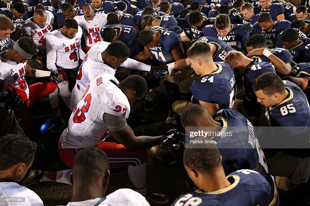 Tight end Jeremiah Gaines #23 of the Southern Methodist Mustangs, linebacker Tyler Goble #54 of the Navy Midshipmen and other players join hands in prayer following an American Athletic Conference football game at Navy-Marine Corps Memorial Stadium on November 14, 2015 in Annapolis, Maryland. The Navy Midshipmen won, 55-14.