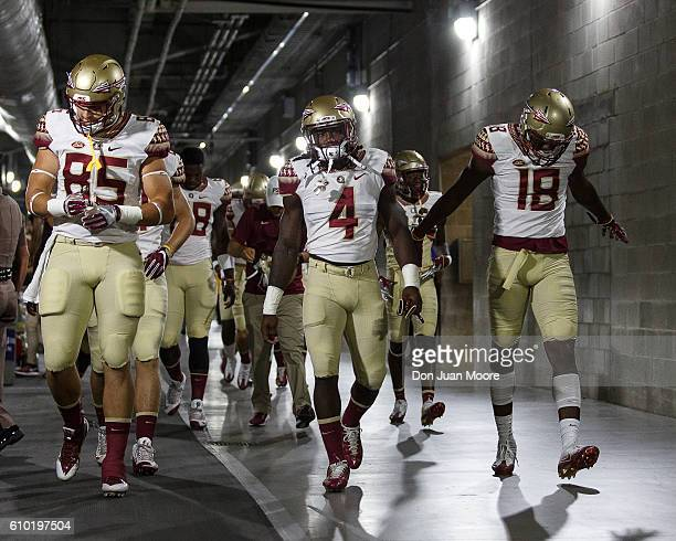 Tight End Jeremy Kerr Runningback Dalvin Cook and Wide Receiver Auden Tate of the Florida State Seminoles lead their teammates from the locker room...