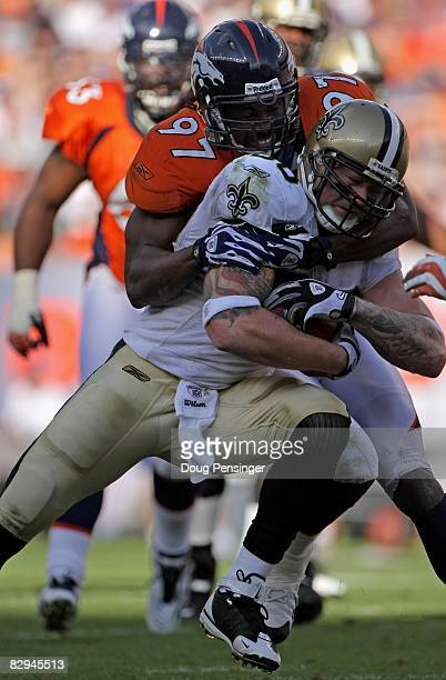 Tight end Jeremy Shockey of the New Orleans Saints makes a reception and is tackled by Boss Bailey of the Denver Broncos during NFL action at Invesco...