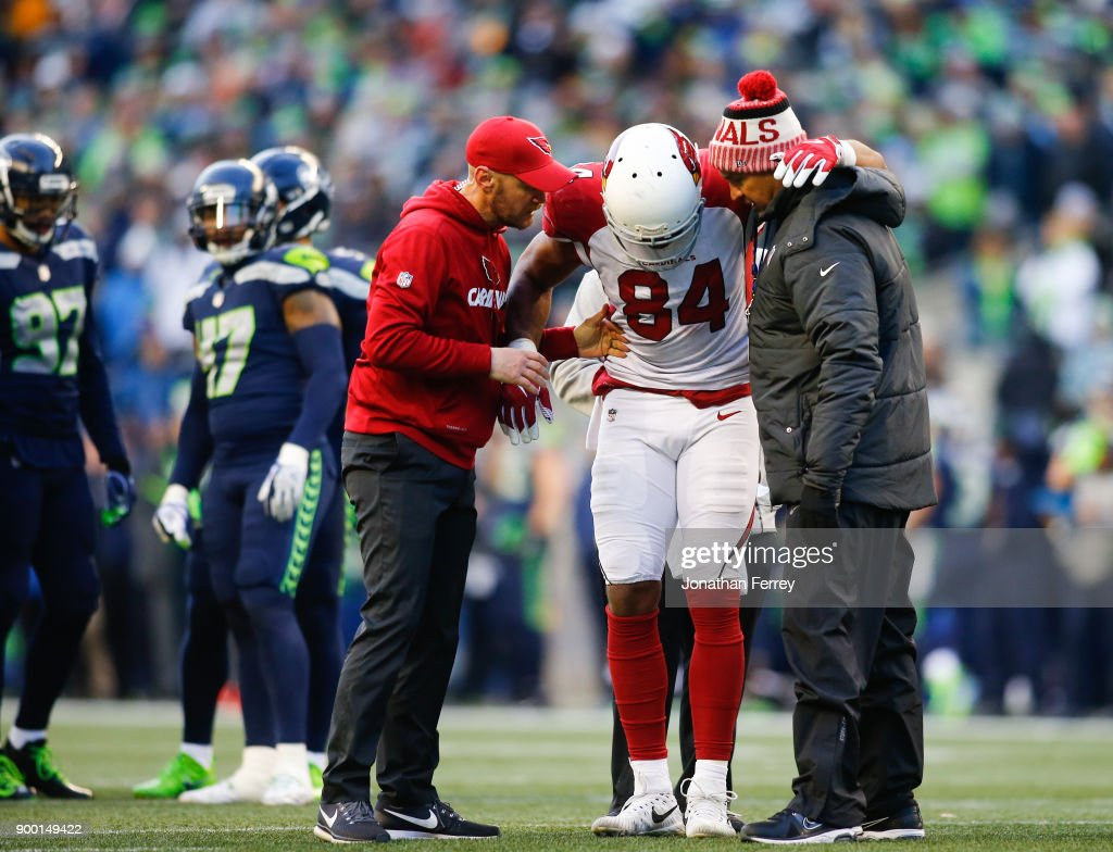 Tight end Jermaine Gresham #84 of the Arizona Cardinals is helped up by staff in the third quarter against the Seattle Seahawks at CenturyLink Field on December 31, 2017 in Seattle, Washington.