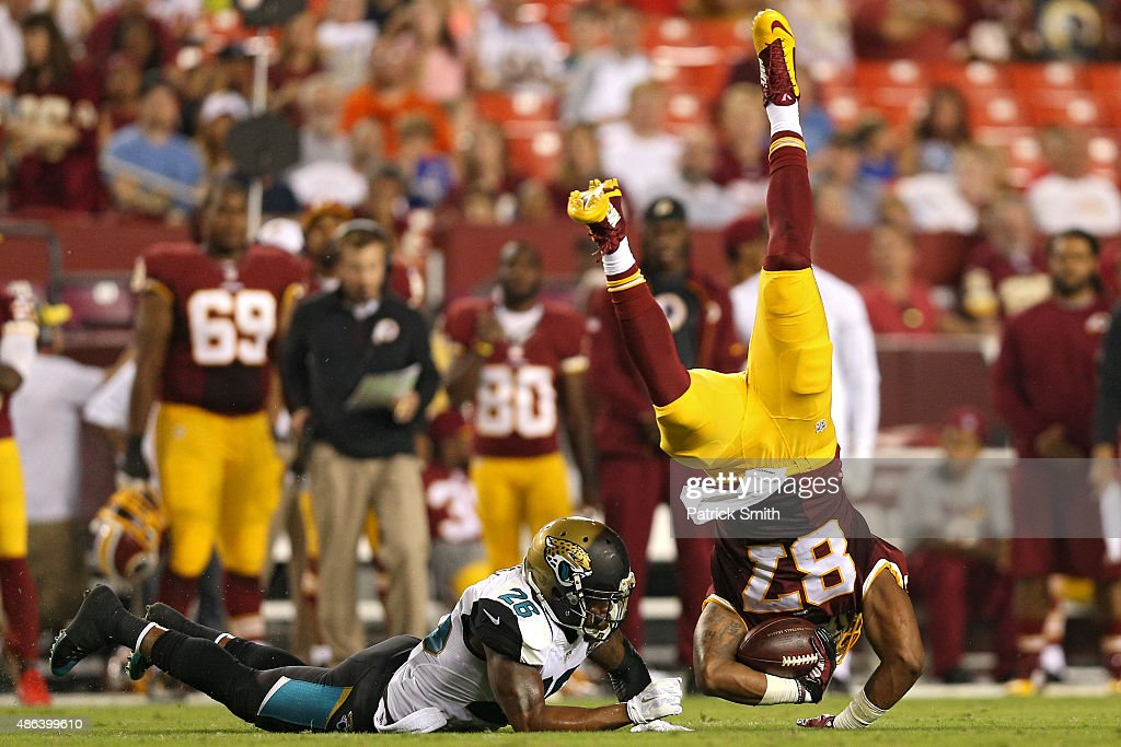 Tight end Je'Ron Hamm #87 of the Washington Redskins is tackled by free safety Josh Evans #26 of the Jacksonville Jaguars in the second quarter at FedExField on September 3, 2015 in Landover, Maryland.