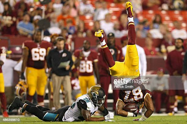 Tight end Je'Ron Hamm of the Washington Redskins is tackled by free safety Josh Evans of the Jacksonville Jaguars in the second quarter at FedExField...