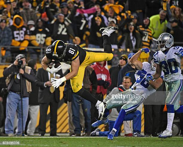 Tight end Jesse James of the Pittsburgh Steelers falls forward after leaping over safety Jeff Heath of the Dallas Cowboys as cornerback Anthony Brown...