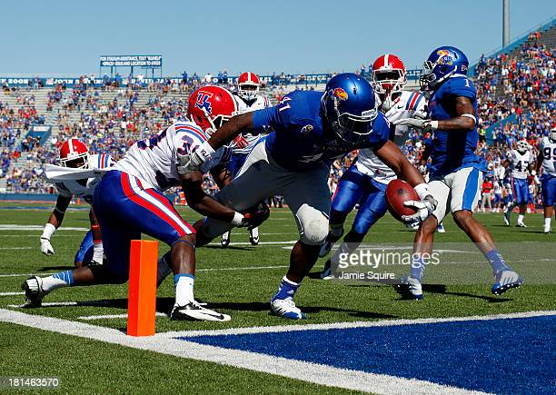 Tight end Jimmay Mundine of the Kansas Jayhawks lunges for a touchdown as defensive back Xavier Woods of the Louisiana Tech Bulldogs defends during...