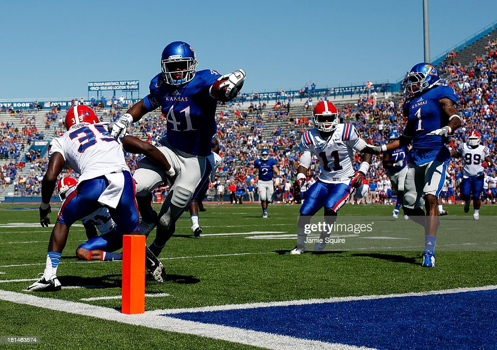 Tight end Jimmay Mundine #41 of the Kansas Jayhawks lunges for a touchdown as defensive back Xavier Woods #39 of the Louisiana Tech Bulldogs defends during the game at Memorial Stadium on September 21, 2013 in Lawrence, Kansas.