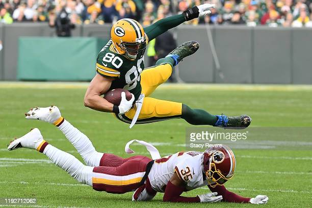 Tight end Jimmy Graham of the Green Bay Packers is tripped up by free safety Montae Nicholson of the Washington Redskins during the game at Lambeau...