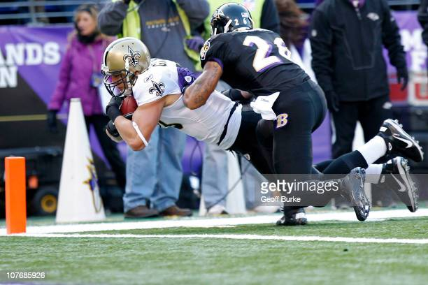 Tight end Jimmy Graham of the New Orleans Saints dives with the ball to score a touchdown as safety Dawan Landry of the Baltimore Ravens defends at...