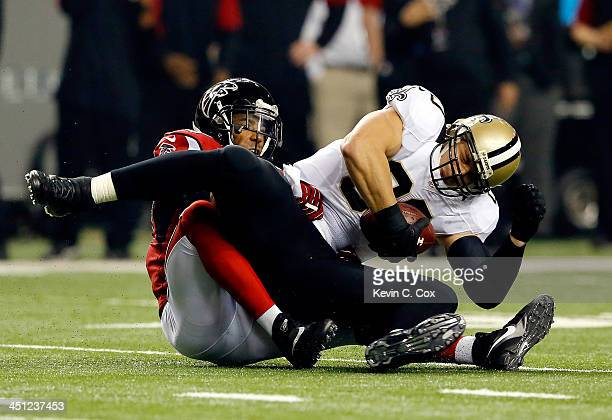 Tight end Jimmy Graham of the New Orleans Saints is tackled by free safety Thomas DeCoud of the Atlanta Falcons during a game at the Georgia Dome on...