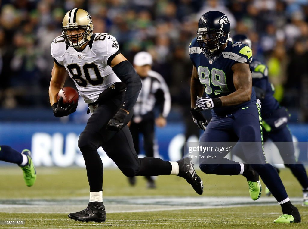 Tight end Jimmy Graham #80 of the New Orleans Saints runs with the ball after a reception as defensive tackle Tony McDaniel #99 of the Seattle Seahawks defends during a game at CenturyLink Field on December 2, 2013 in Seattle, Washington.
