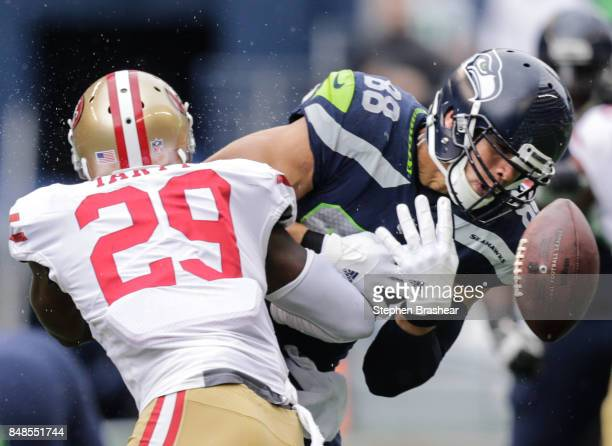 Tight end Jimmy Graham of the Seattle Seahawks drops the ball while being tackled by safety Jaquiski Tartt of the San Francisco 49ers in the first...