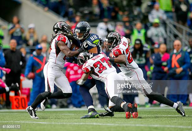 Tight end Jimmy Graham of the Seattle Seahawks is wrapped up by cornerback Desmond Trufant safety Ricardo Allen and safety Keanu Neal of the Atlanta...