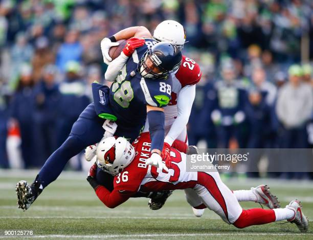 Tight end Jimmy Graham of the Seattle Seahawks makes a 20 yard reception on 4th down against safety Budda Baker of the Arizona Cardinals and Justin...