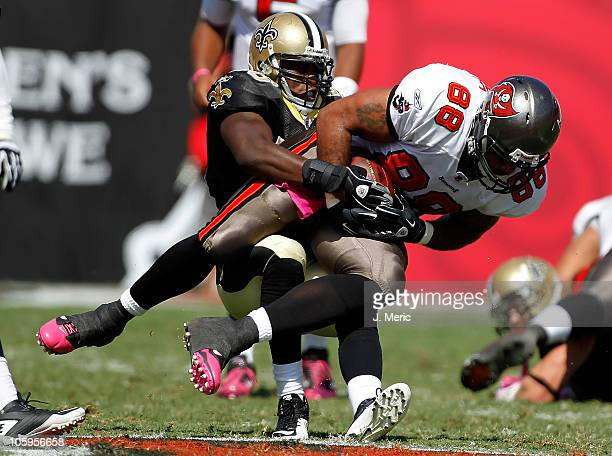 Tight end John Gilmore of the Tampa Bay Buccaneers is tackled by linebacker Marvin Mitchell of the New Orleans Saints during the game at Raymond...