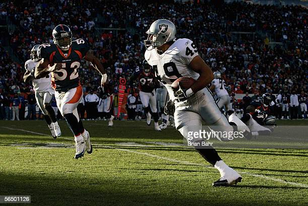 Tight end John Paul Foschi of the Oakland Raiders carries the ball downfield as linebacker Ian Gold of the Denver Broncos gives chase on December 24...