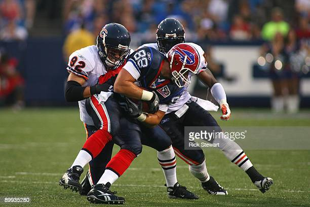 Tight end Jonathan Stupar of the Buffalo Bills is tackled by Hunter Hillenmeyer and Jamar Williams of the Chicago Bears during the preseason game on...
