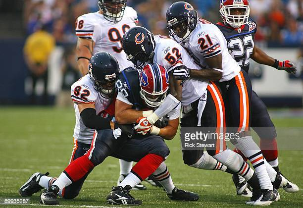 Tight end Jonathan Stupar of the Buffalo Bills is tackled by Hunter Hillenmeyer Jamar Williams and Corey Graham of the Chicago Bears during the...
