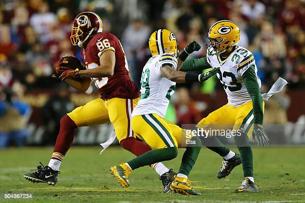 Tight end Jordan Reed of the Washington Redskins carries the ball against cornerback Casey Hayward and strong safety Micah Hyde of the Green Bay...