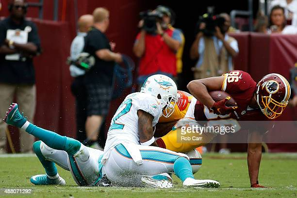 Tight end Jordan Reed of the Washington Redskins is tackled by cornerback Jamar Taylor of the Miami Dolphins in the first half during a game at...