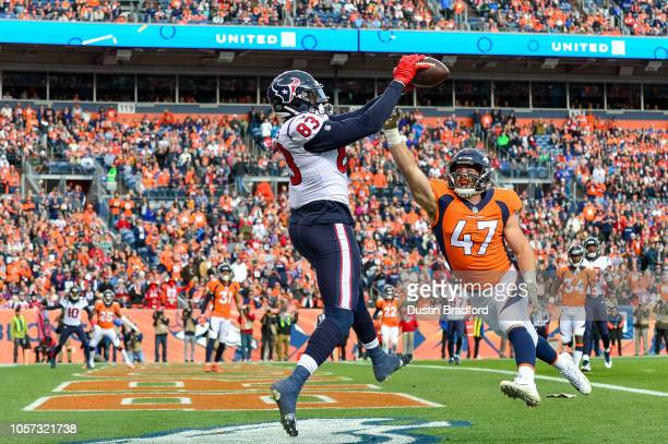 Tight end Jordan Thomas of the Houston Texans catches a pass for a first quarter touchdown under coverage by inside linebacker Josey Jewell of the...
