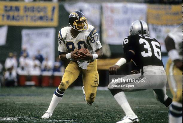 Tight End Kellen Winslow of the San Diego Chargers looking to avoid the tackle of defensive back Mike Davis of the Oakland Raiders circa 1980 during...