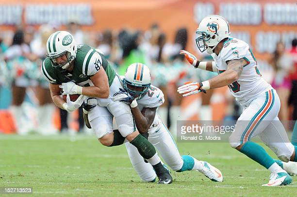 Tight end Konrad Reuland of the New York Jets carries the ball after catching a pass and is tackled by cornerback Sean Smith of the Miami Dolphins...