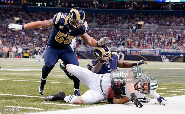 tight end Konrad Reuland of the New York Jets falls to the ground after being tackled by middle linebacker James Laurinaitis and free safety Quintin...