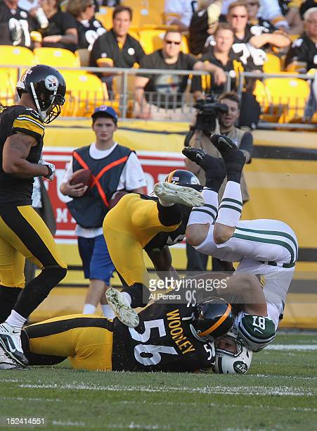 Tight End Konrad Reuland of the New York Jets is dumped on his head after a catch by Linebacker Lamarr Woodley of the Pittsburgh Steelers at Heinz...