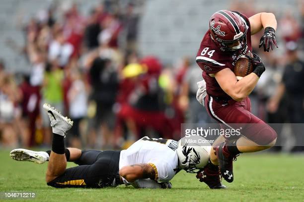 Tight end Kyle Markway of the South Carolina Gamecocks is tripped up by safety Cam Hilton of the Missouri Tigers during the football game at...