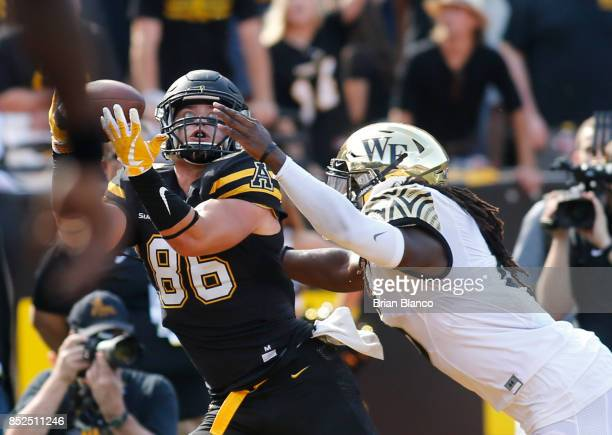 Tight end Levi Duffield of the Appalachian State Mountaineers hauls in a pass from quarterback Taylor Lamb in front of linebacker Jaboree Williams of...