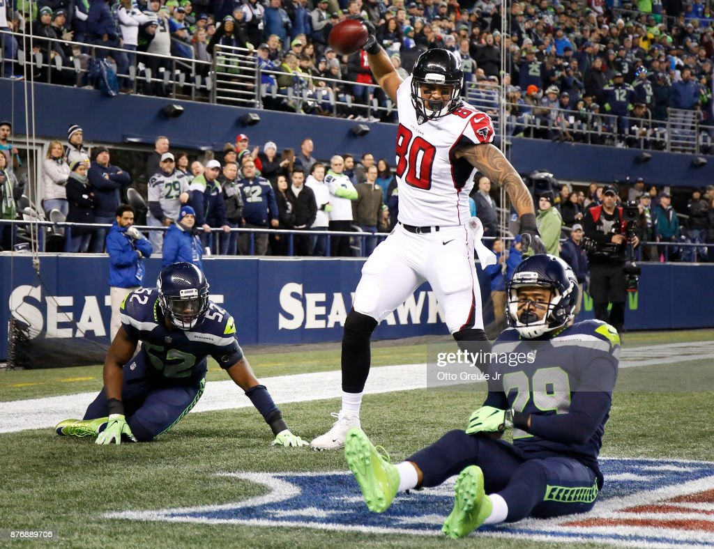 Tight end Levine Toilolo #80 of the Atlanta Falcons spikes the ball to celebrate his 25 yard touchdown as linebacker Terence Garvin #52 of the Seattle Seahawks and Earl Thomas #29 react during the third quarter of the game at CenturyLink Field on November 20, 2017 in Seattle, Washington.