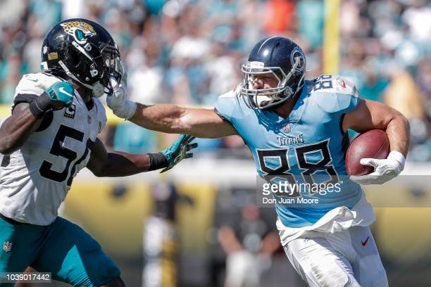 Tight End Luke Syocker of the Tennessee Titans gives a stiff arm in the face mask of Linebacker Telvin Smith of the Jacksonville Jaguars during the...