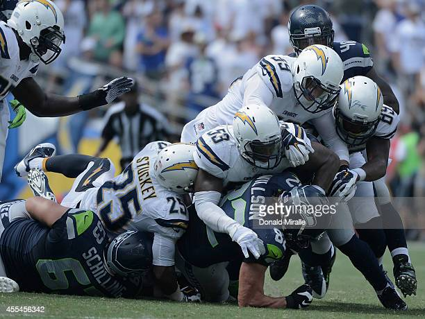 Tight end Luke Willson of the Seattle Seahawks is tackled by defensive back Darrell Stuckey inside linebacker Kavell Conner and inside linebacker...