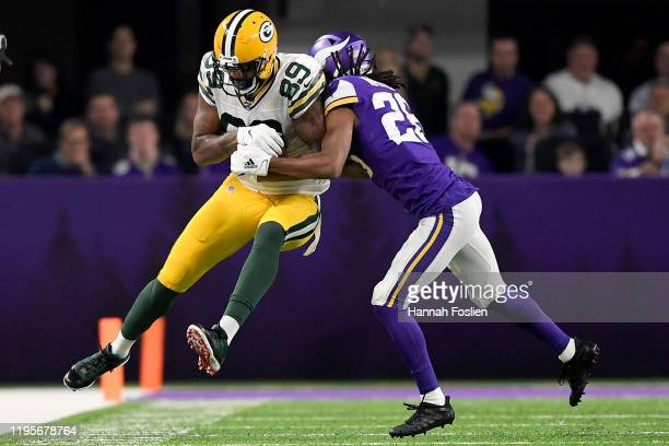 Tight end Marcedes Lewis of the Green Bay Packers is forced out by cornerback Trae Waynes of the Minnesota Vikings in the second quarter of the game...