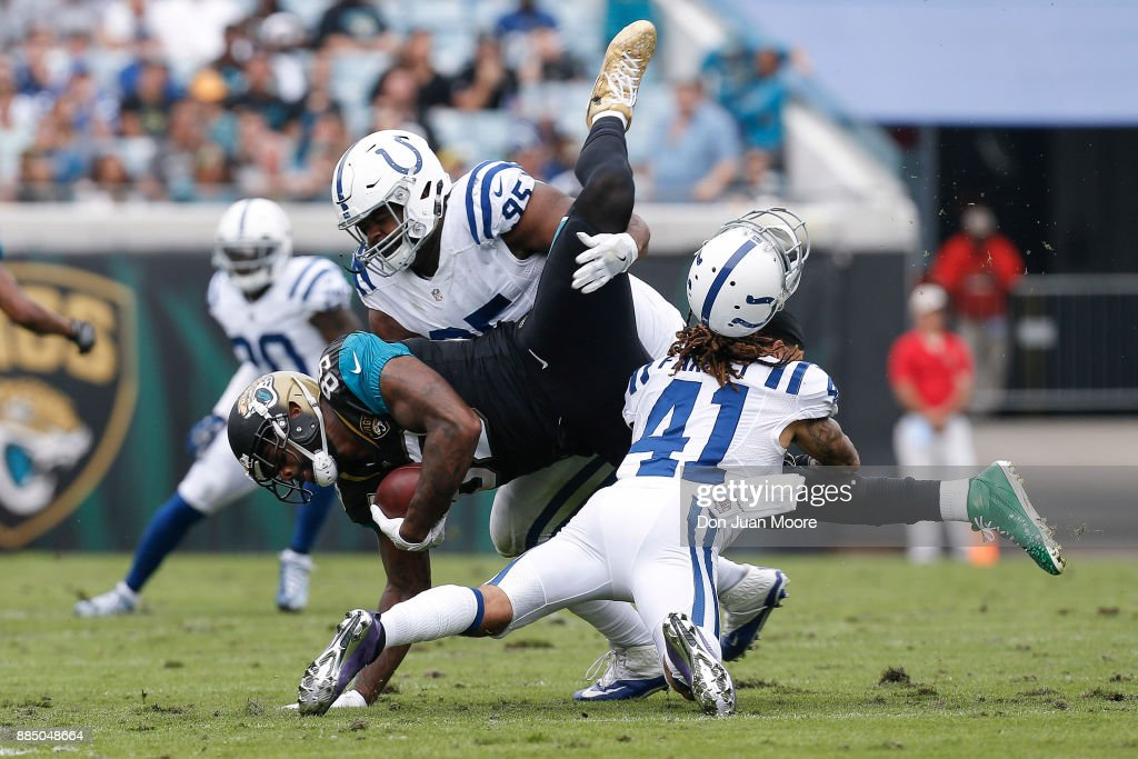 Tight End Marcedes Lewis #89 of the Jacksonville Jaguars is tackled by Defensive Tackle Johnathan Hankins #95 and Safety Matthias Farley #41, who looses his helmet, during the game against the Indianapolis Colts at EverBank Field on December 3, 2017 in Jacksonville, Florida. The Jaguars defeated the Colts 30 to 10.