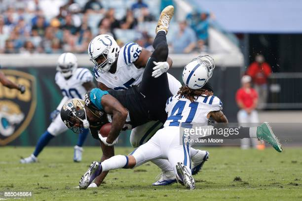 Tight End Marcedes Lewis of the Jacksonville Jaguars is tackled by Defensive Tackle Johnathan Hankins and Safety Matthias Farley who looses his...