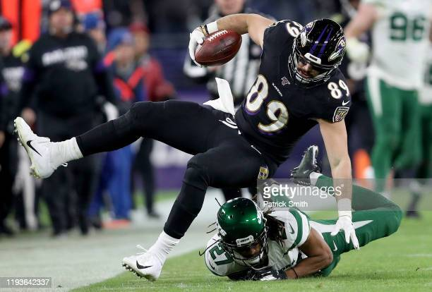 Tight end Mark Andrews of the Baltimore Ravens is tripped by cornerback Darryl Roberts of the New York Jets during the game at MT Bank Stadium on...