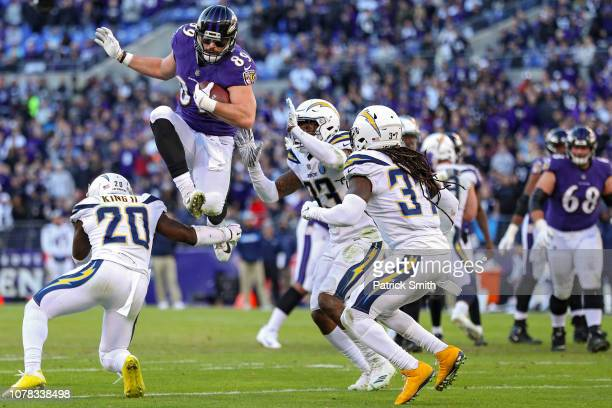 Tight end Mark Andrews of the Baltimore Ravens leaps over defensive back Desmond King of the Los Angeles Chargers in the fourth quarter during the...