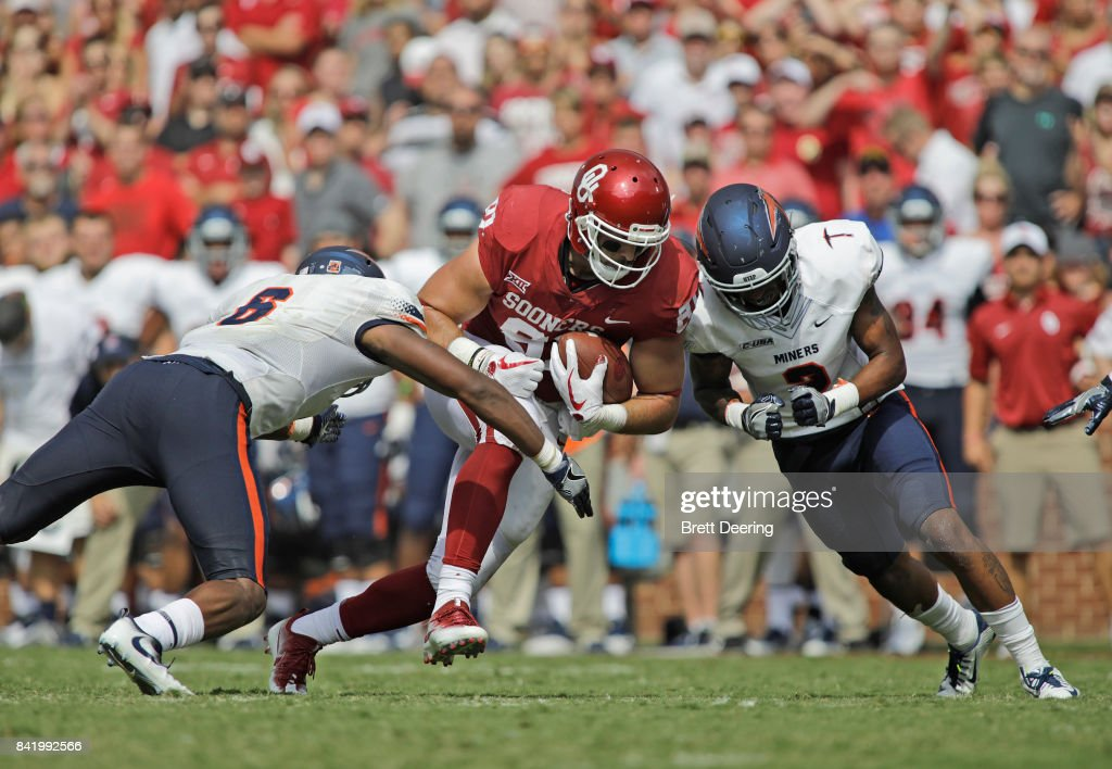 tight end Mark Andrews #81 of the Oklahoma Sooners is hit by linebacker Dylan Parsee #6 and defensive back Michael Lewis #2 of the UTEP Miners at Gaylord Family Oklahoma Memorial Stadium on September 2, 2017 in Norman, Oklahoma. Oklahoma defeated UTEP