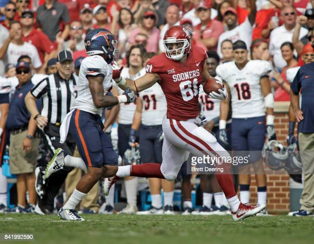 Tight end Mark Andrews of the Oklahoma Sooners stiff arms defensive back Michael Lewis of the UTEP Miners at Gaylord Family Oklahoma Memorial Stadium...