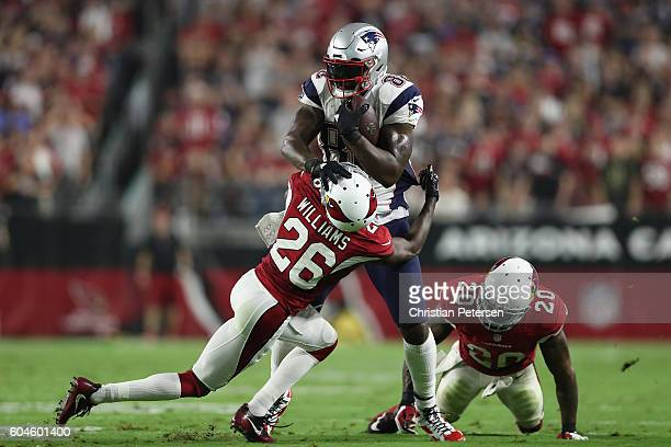 Tight end Martellus Bennett of the New England Patriots is tackled by cornerback Brandon Williams of the Arizona Cardinals after a reception during...