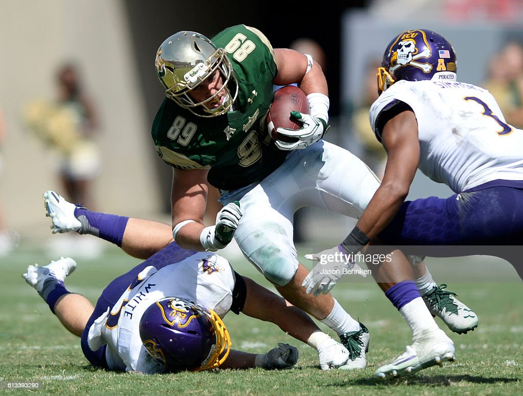 Tight end Mitchell Wilcox #89 of the South Florida Bulls is tripped up by linebacker Cam White #55 of the East Carolina Pirates during the 3rd quarter at Raymond James Stadium on October 8, 2016 in Tampa, Florida.