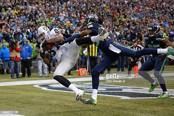 Tight end Mychal Rivera of the Oakland Raiders makes a touchdown catch against cornerback Richard Sherman of the Seattle Seahawks in the third...