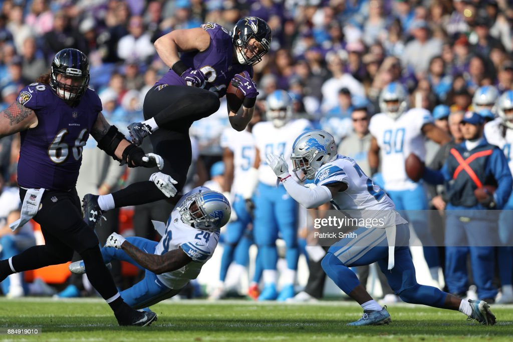 Tight End Nick Boyle #86 of the Baltimore Ravens leaps over cornerback Nevin Lawson #24 of the Detroit Lions in the first quarter at M&T Bank Stadium on December 3, 2017 in Baltimore, Maryland.