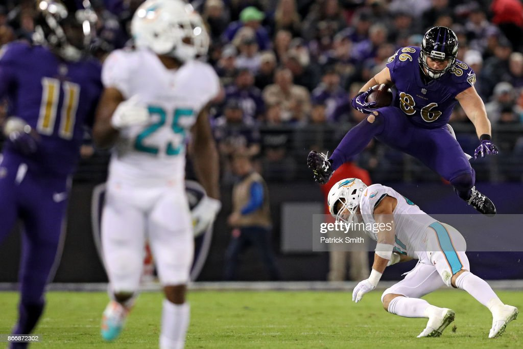 Tight End Nick Boyle #86 of the Baltimore Ravens leaps over middle linebacker Kiko Alonso #47 of the Miami Dolphins in the second quarter at M&T Bank Stadium on October 26, 2017 in Baltimore, Maryland.