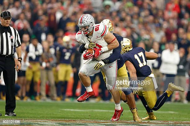 Tight end Nick Vannett of the Ohio State Buckeyes is hit by defensive lineman Isaac Rochell of the Notre Dame Fighting Irish during the fourth...