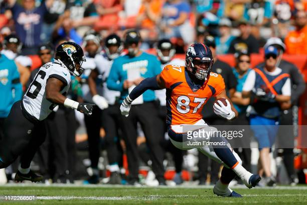 Tight end Noah Fant of the Denver Broncos runs with the football past linebacker Quincy Williams of the Jacksonville Jaguars on his way to a...