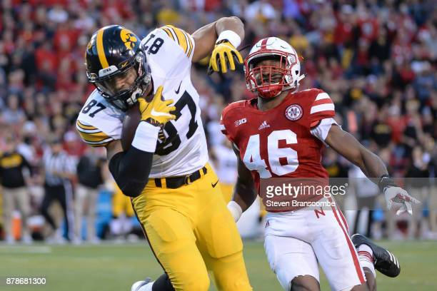 Tight end Noah Fant of the Iowa Hawkeyes grabs a pass against defensive end Joshua Kalu of the Nebraska Cornhuskers at Memorial Stadium on November...