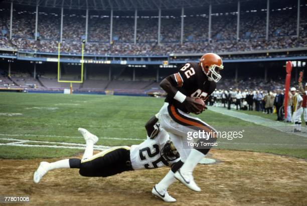 Tight end Ozzie NEwsome of the Cleveland Browns catches a touchdown pass despite the efforts of cornerback Johnny Poe of the New Orleans Saints...